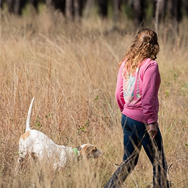 Girl walking with dog in field
